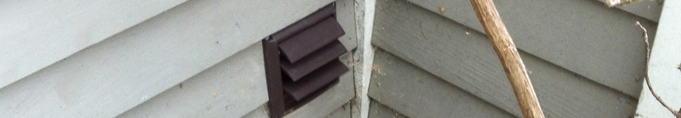 Dark brown dryer vent on the outside of a house with gray siding. Branches appear in the right side of the photo.